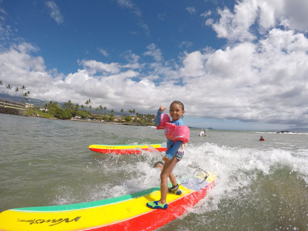 little girl surfing throwing shaka