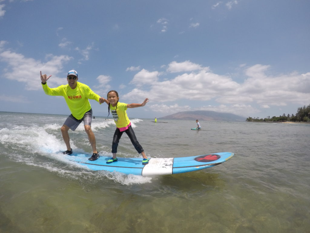 father and daughter surfing on Maui